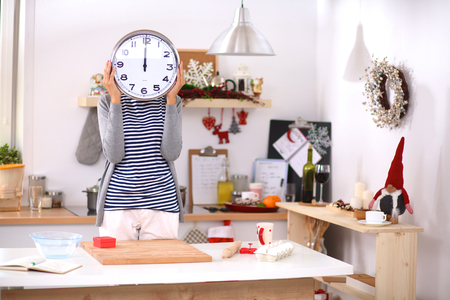 Happy young woman showing clock in christmas decorated kitchen .