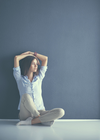 Young woman sitting on the floor near dark wall.