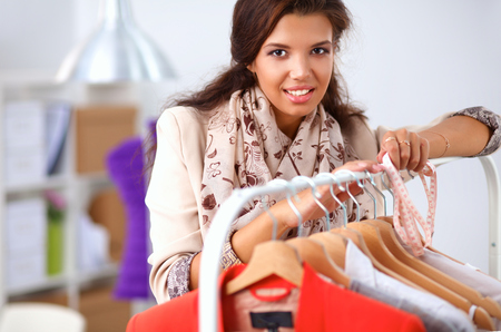 Beautiful young stylist near rack with hangers in office