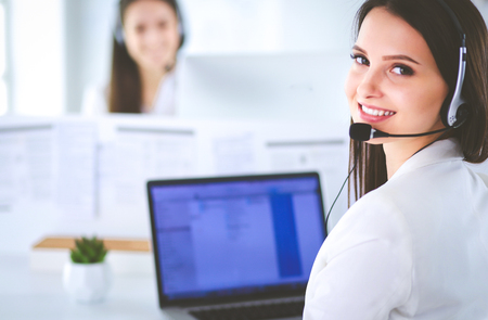Photo pour Smiling businesswoman or helpline operator with headset and computer at office - image libre de droit
