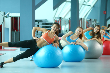 Photo for Sporty people sitting on exercise mats at a bright fitness studio. Sporty girls - Royalty Free Image