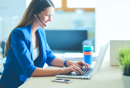 Photo pour Portrait of beautiful business woman working at her desk with headset and laptop.. - image libre de droit