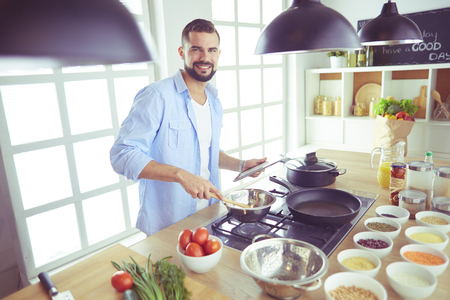 Photo pour Man following recipe on digital tablet and cooking tasty and healthy food in kitchen at home - image libre de droit