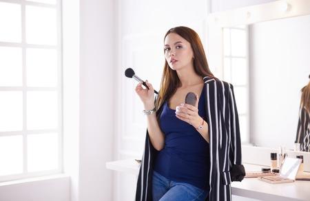 Foto de Closeup portrait of woman with makeup brush near face - Imagen libre de derechos