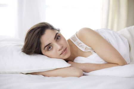 Photo pour Pretty woman lying down on her bed at home - image libre de droit