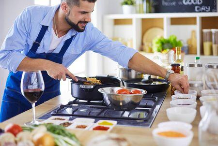 Photo pour Man preparing delicious and healthy food in the home kitchen - image libre de droit