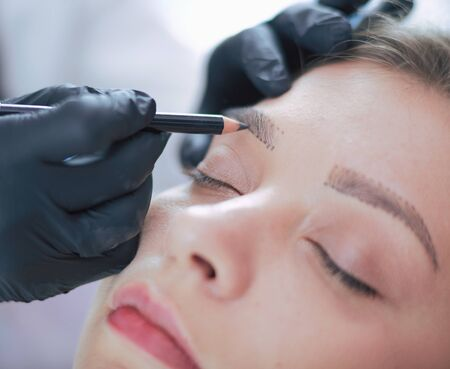 Photo for Cosmetologist applying permanent make up on eyebrows. - Royalty Free Image