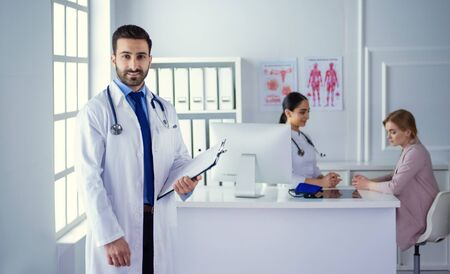 Photo pour Smiling doctor man standing in front of his team and patient - image libre de droit