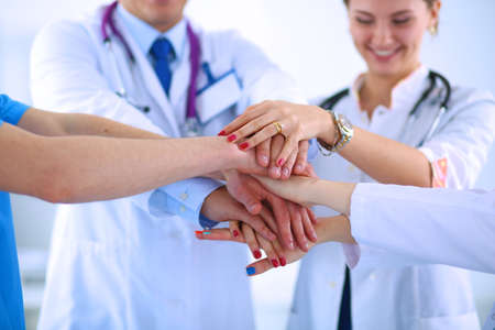 Photo pour Doctors and nurses in a medical team stacking hands - image libre de droit