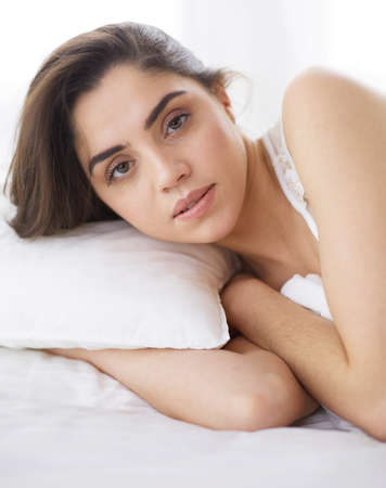 Photo for Pretty woman lying down on her bed at home - Royalty Free Image