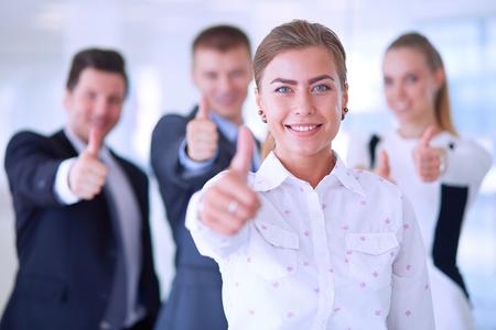 Photo pour Happy business team showing thumbs up in office . - image libre de droit