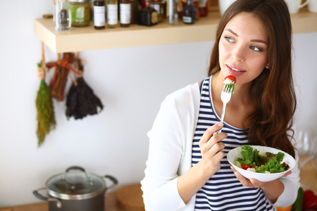 Young woman eating salad and holding a mixed salad .