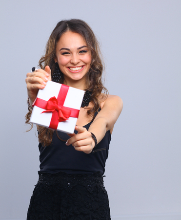 Photo pour Young woman happy smile hold gift box in hands, isolated over gray - image libre de droit