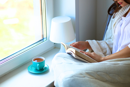 Foto de Young woman at home sitting near window relaxing in her living room reading book and drinking coffee or tea . - Imagen libre de derechos
