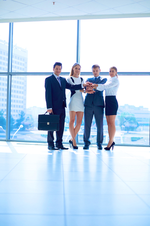 Photo pour Business people with their hands together in a circle - image libre de droit