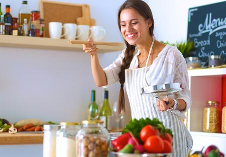 Foto de Cooking woman in kitchen with wooden spoon. - Imagen libre de derechos