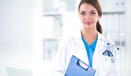 Portrait of young woman doctor with white coat standing in hospital