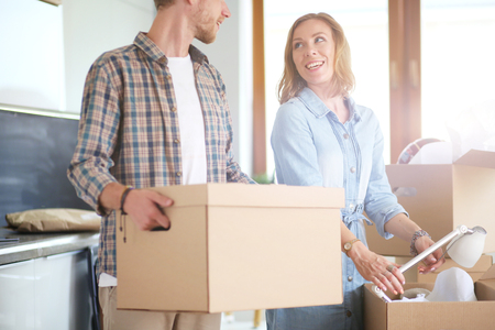 Photo pour Couple unpacking cardboard boxes in their new home. Young couple. - image libre de droit