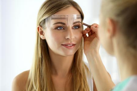 Foto de Permanent makeup for eyebrows. Closeup of beautiful woman with thick brows in beauty salon. - Imagen libre de derechos