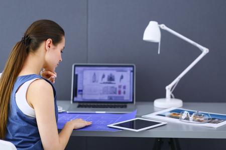 Foto de Young woman sitting at the desk with instruments, plan and laptop. - Imagen libre de derechos