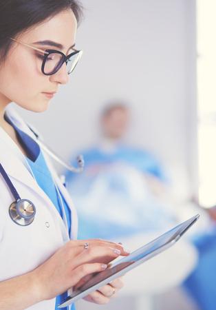 Foto de Female doctor using tablet computer in hospital lobby - Imagen libre de derechos
