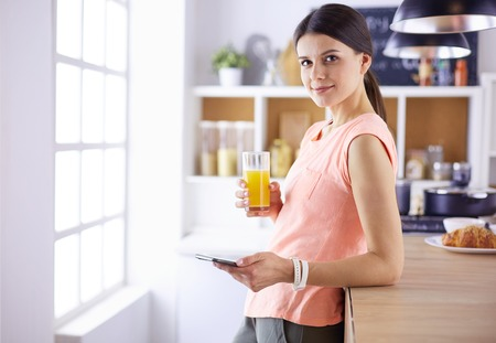 Foto per Smiling pretty woman looking at mobile phone and holding glass of orange juice while having breakfast in a kitchen. - Immagine Royalty Free