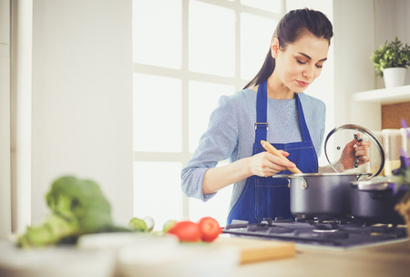 Photo for Cooking woman in kitchen with wooden spoon - Royalty Free Image