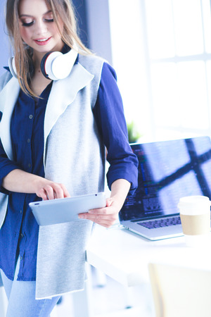 Photo pour Young confident businesswoman working at office desk and typing with a laptop - image libre de droit