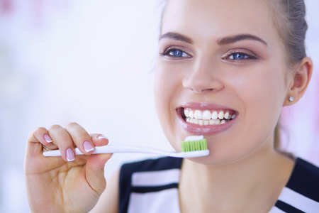 Photo pour Young pretty girl maintaining oral hygiene with toothbrush. - image libre de droit