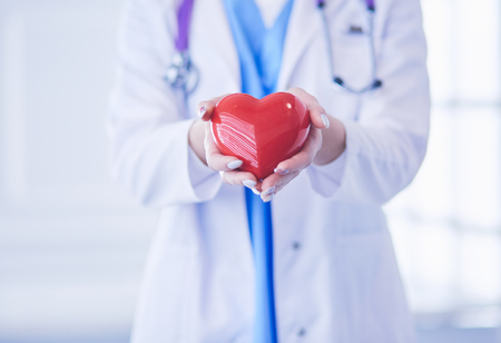 Photo pour Female doctor with stethoscope holding heart in her arms. Healthcare and cardiology concept in medicine - image libre de droit