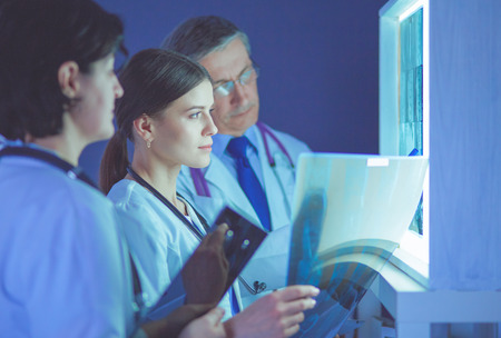 Photo pour Group of doctors examining x-rays in a clinic, thinking of a diagnosis - image libre de droit
