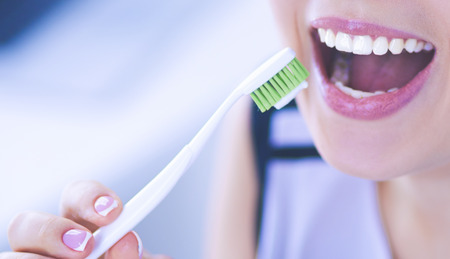 Photo for Young pretty girl maintaining oral hygiene with toothbrush. - Royalty Free Image