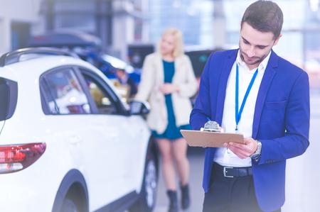 Photo pour Dealer stands near a new car in the showroom - image libre de droit