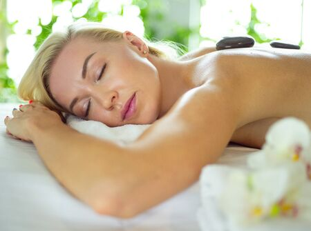 Photo pour Young woman in spa salon, getting stones massage. - image libre de droit
