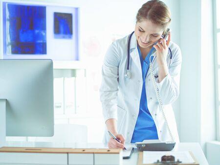 Foto de Portrait of a beautiful smiling nurse talking on the phone - Imagen libre de derechos