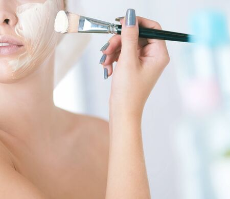 Photo pour A picture of a young woman applying face powder in the bathroom - image libre de droit
