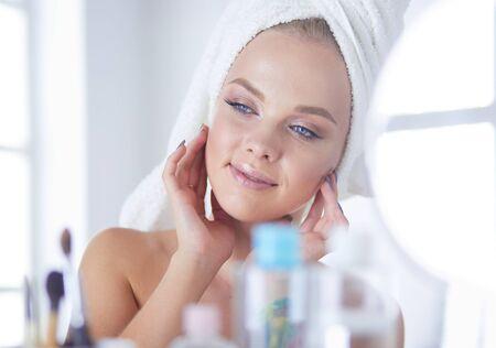 Photo pour Young woman in bathrobe looking in bathroom mirror - image libre de droit