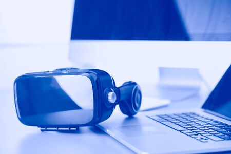 Photo pour Virtual reality goggles on desk with laptop. business. 3d technology. - image libre de droit