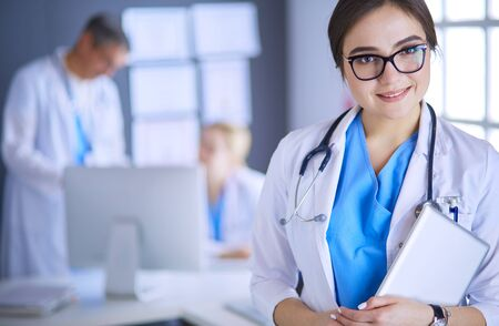 Photo pour Female doctor using tablet computer in hospital lobby - image libre de droit