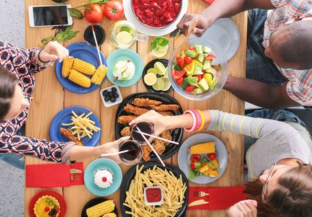 Photo pour Top view of group of people having dinner together while sitting at wooden table. Food on the table. People eat fast food. - image libre de droit