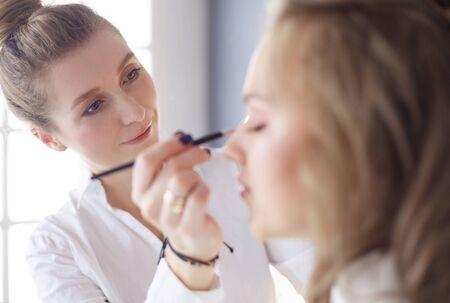 Photo pour beautiful young model woman getting fashion make-up - image libre de droit