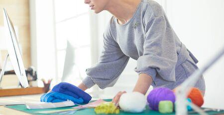 Photo pour Woman designer in workshop looking at laptop. - image libre de droit