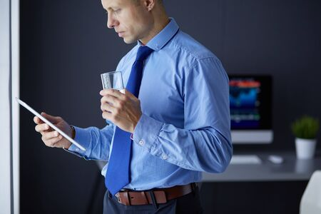 Photo pour Smiling businessman with touchpad standing at workplace in office - image libre de droit