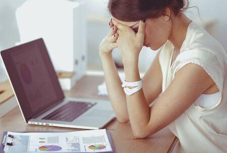 Photo pour Portrait of tired young business woman with laptop computer - image libre de droit
