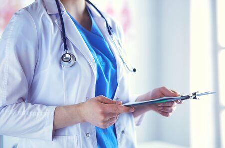 Photo pour Woman doctor standing with folder at hospital. - image libre de droit