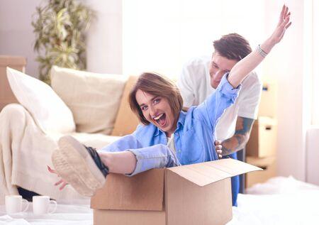 Foto de Couple having fun laughing moving into new home, young woman riding sitting in cardboard box while man pushing it - Imagen libre de derechos