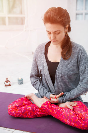 Woman sitting in lotus asana and doing yoga meditation with spiritual accessories, candles and Buddha statue. Concept of physical and mental health, relax and well being