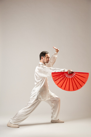 Photo for Senior master practicing qi qong taijiquan at studio. Breathing exercise and martial art moves, traditional chinese qi energy management gymnastics - Royalty Free Image