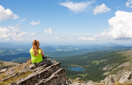 girl sits on a rock and looks at mountain lake