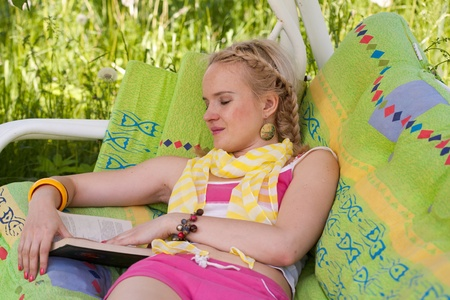 young woman reads the book lying in a hammock